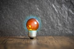 concepto de la idea con la bombilla anaranjada y la luz azul de madera con el fondo oscuro fotografía de archivo libre de regalías