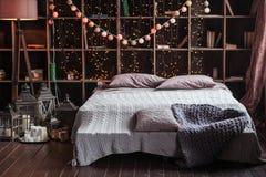 Concepto de la intimidad, de la comodidad, del interior y de los días de fiesta - dormitorio acogedor con las luces de la cama y  Imagen de archivo libre de regalías