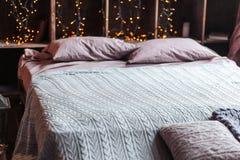 Concepto de la intimidad, de la comodidad, del interior y de los días de fiesta - dormitorio acogedor con las luces de la cama y  Imagen de archivo