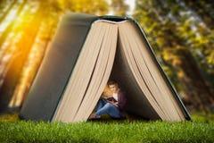 Concepto de la lectura, hombre que se sienta debajo del libro grande Imágenes de archivo libres de regalías