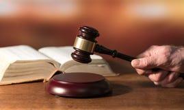 Concepto de la ley con la mano que sostiene un mazo del juez fotos de archivo
