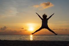 Concepto de la libertad con el adolescente joven de la silueta feliz y el salto Fotografía de archivo libre de regalías