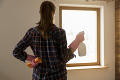 Concepto de la limpieza La mujer que se coloca antes de la ventana con la limpieza del paño y de ventana rocía listo para lavar l imagen de archivo