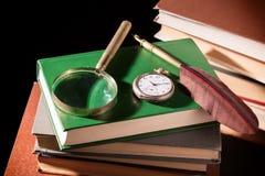 Concepto de la literatura Los libros viejos con la pluma de la pluma, la lupa y el viejo vintage registran en fondo negro Fotografía de archivo libre de regalías