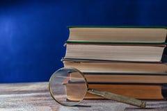 Concepto de la literatura Lupa cerca de los libros viejos en fondo azul marino Imagenes de archivo