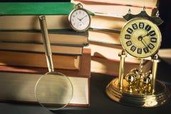 Concepto de la literatura Lupa cerca de los relojes del vintage y de los libros viejos contra fondo negro Fotografía de archivo libre de regalías