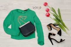 Concepto de la manera Blusa verde, bolso, gafas de sol, zapatos negros y tulipanes rosados Visión superior, fondo de madera liger Fotos de archivo libres de regalías