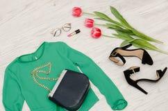 Concepto de la manera Blusa verde, bolso, gafas de sol, zapatos negros y tulipanes rosados Visión superior, fondo de madera liger Imagen de archivo libre de regalías