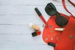 Concepto de la manera Bolso rojo, cosas femeninas, productos cosm?ticos, sunglass, pendientes en fondo de madera con el copyspace imagen de archivo libre de regalías