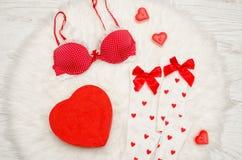 Concepto de la manera Caja roja en forma de corazón con la ropa interior del cordón, medias blancas con los arcos, sujetador rojo imagen de archivo