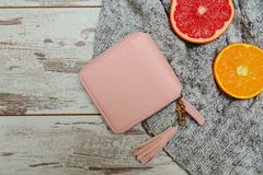 Concepto de la manera Pequeño monedero rosado del ` s de las mujeres, un suéter, y fruta cítrica en un fondo de madera Fotos de archivo libres de regalías