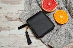 Concepto de la manera Un pequeños monedero y fruta cítrica negros femeninos en un suéter, un fondo de madera Fotografía de archivo libre de regalías