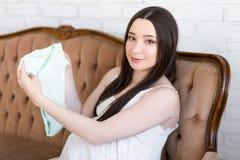 Concepto de la maternidad - mujer embarazada hermosa joven que se sienta en v Fotos de archivo libres de regalías