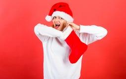 Concepto de la media de la Navidad De la muchacha de la cara del control regalo alegre hacia fuera en calcetín de la Navidad Muje imagen de archivo