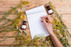 Concepto de la medicina alternativa - la mano escribe una receta en libreta encendido Imágenes de archivo libres de regalías