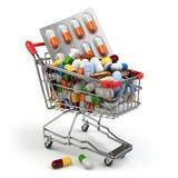 Concepto de la medicina de la farmacia Carro de la compra con las píldoras y las cápsulas Foto de archivo libre de regalías