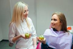 Concepto de la medicina - doctor de sexo femenino que da una manzana al paciente fotografía de archivo libre de regalías
