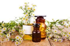Concepto de la medicina herbaria - botellas con la manzanilla y el aceite en woode Foto de archivo libre de regalías