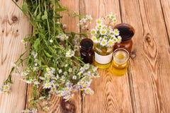 Concepto de la medicina herbaria - botellas con la manzanilla y el aceite en woode Imágenes de archivo libres de regalías