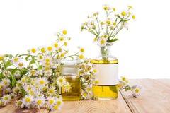 Concepto de la medicina herbaria - botellas con la manzanilla y el aceite en woode Imagen de archivo libre de regalías