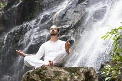 Concepto de la meditaci?n de la yoga de la salud Hombre joven que se sienta en la posici?n de loto respecto a la roca debajo de l imagen de archivo