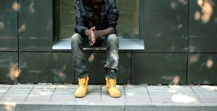 Concepto de la moda de la calle, hombre africano en chaqueta negra, vaqueros y botas Imágenes de archivo libres de regalías
