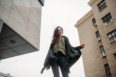Concepto de la moda: chica joven hermosa con el pelo largo, los vidrios, los labios rojos que se colocan cerca de la pared modern Fotografía de archivo libre de regalías