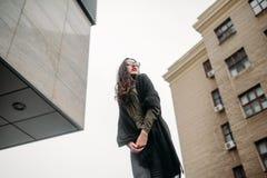 Concepto de la moda: chica joven hermosa con el pelo largo, los vidrios, los labios rojos que se colocan cerca de la pared modern Fotos de archivo libres de regalías