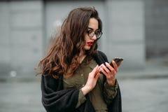 Concepto de la moda: chica joven hermosa con el pelo largo, los vidrios, los labios rojos que se colocan cerca de la pared modern Imagen de archivo libre de regalías