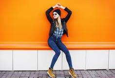 Concepto de la moda de la calle - muchacha fresca elegante en estilo del negro de la roca Imagenes de archivo