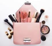 Concepto de la moda: Endecha plana del bolso de cuero rosado de la mujer abierto hacia fuera con los cosméticos y los accesorios  foto de archivo