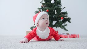 Concepto de la Navidad Bebé lindo en el traje de Santa Claus, mirando un regalo metrajes