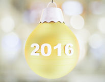Concepto 2016 de la Navidad con la bola amarilla del árbol de navidad Foto de archivo
