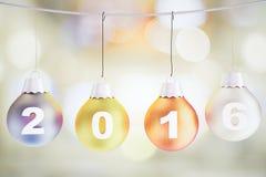 Concepto 2016 de la Navidad con las bolas multicoloras del árbol de navidad encendido Imagen de archivo libre de regalías