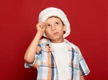 Concepto de la Navidad de las vacaciones de invierno - el muchacho en el sombrero de santa tiene idea en fondo rojo Foto de archivo libre de regalías
