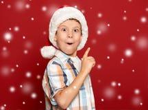 Concepto de la Navidad de las vacaciones de invierno - el muchacho en el sombrero de santa tiene idea encendido Fotografía de archivo libre de regalías