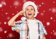 Concepto de la Navidad de las vacaciones de invierno - el muchacho en el sombrero de santa tiene idea encendido Foto de archivo libre de regalías