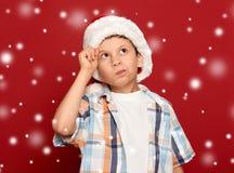 Concepto de la Navidad de las vacaciones de invierno - el muchacho en el sombrero de santa tiene idea encendido Imagen de archivo