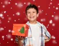 Concepto de la Navidad de las vacaciones de invierno - muchacho con el regalo de la caja en la parte posterior del rojo Fotografía de archivo libre de regalías