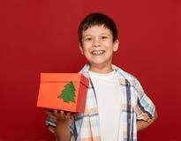 concepto de la Navidad de las vacaciones de invierno - muchacho con el regalo de la caja en rojo Imágenes de archivo libres de regalías
