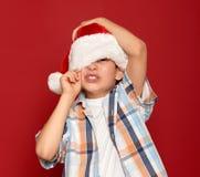 Concepto de la Navidad de las vacaciones de invierno - muchacho en cierre del sombrero de santa un ojo en rojo Foto de archivo libre de regalías