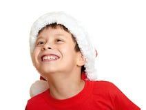 Concepto de la Navidad de las vacaciones de invierno - muchacho en el retrato del sombrero de santa en blanco aislado Foto de archivo