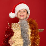 Concepto de la Navidad de las vacaciones de invierno - muchacho en el sombrero de santa con la caja de regalo de oro en rojo Foto de archivo