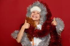 concepto de la Navidad de las vacaciones de invierno - muchacho en el sombrero de santa que se divierte en rojo Fotos de archivo libres de regalías