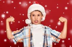 Concepto de la Navidad de las vacaciones de invierno - muchacho en músculo de la demostración del sombrero de santa Imagen de archivo
