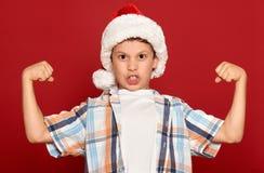 Concepto de la Navidad de las vacaciones de invierno - muchacho en músculo de la demostración del sombrero de santa en rojo Fotos de archivo libres de regalías