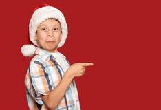 Concepto de la Navidad de las vacaciones de invierno - muchacho en punto del sombrero de santa su finger en rojo Foto de archivo