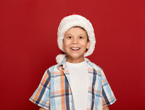 Concepto de la Navidad de las vacaciones de invierno - muchacho en retrato del sombrero de santa en fondo rojo Imagenes de archivo