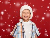 Concepto de la Navidad de las vacaciones de invierno - muchacho en retrato del sombrero de santa encendido Fotografía de archivo libre de regalías