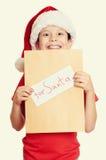 Concepto de la Navidad de las vacaciones de invierno - muchacho en sombrero con la letra a santa en blanco aislado Foto de archivo